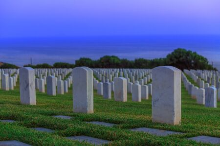 Cemetery graveyard white tombstones at evening. American war cemetery in Point Loma, San Diego, California, United States with rows of gravestones oriented towards the ocean.
