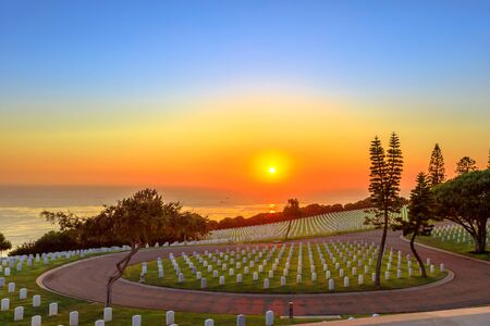 Cemetery graveyard white tombstones at sunset sky. American war cemetery in Point Loma, San Diego, California, United States with rows of gravestones oriented towards the ocean. 写真素材