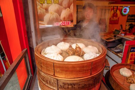Yokohama, Japan - April 21, 2017: closeup of cook preparing asian steaming dumplings or dim sum, cooking in a wooden steamer in Yokohama Chinatown, the Japans largest Chinatown, central Yokohama 스톡 콘텐츠 - 143450229