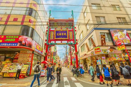 Yokohama, Japan - April 21, 2017: people and asian girls in school uniform in front of gate in Yokohama Chinatown, the Japans largest Chinatown, central Yokohama. Urban pedestrian street walking area