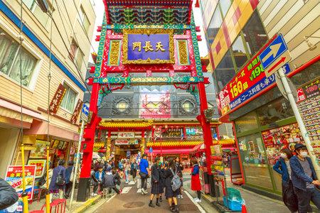 Yokohama, Japan - April 21, 2017: chinese people wearing mask and asian girls in school uniform near the gate in Yokohama Chinatown, the Japans largest Chinatown. Urban pedestrian street walking area 에디토리얼