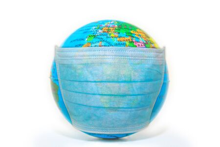 blue disposable face mask on a sick world globe isolated on white background. Concept of epidemic flu and pandemic emergency worldwide for COVID 19 coronavirus. European and African face of the world.