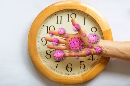 COVID-19 virus cells on hand with a clock on background. Conceptual: no more time, deadline, now its too late. Severe acute respiratory syndrome coronavirus 2 or SARS-CoV-2 has become a pandemic.