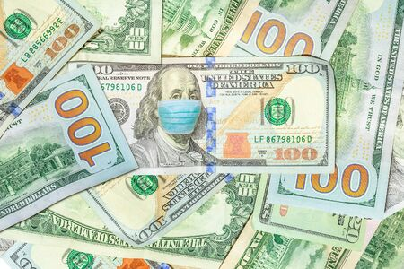 Face mask on Benjamin Franklin American 100 dollars banknote. Business concept of Covid 19-NCP virus pandemic in the United States. Covid-19 Coronavirus outbreak and the American money market.