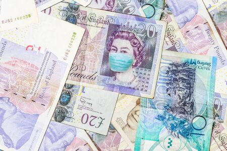 Face mask on 20 English pound banknote. Business concept of Covid 19-NCP virus pandemic in the United Kingdom. Covid-19 Coronavirus outbreak and the British money market.