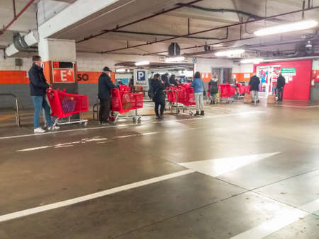 Bologna, Italy - April 24, 2020: people queue with shopping carts from entrance underground parking of Esselunga supermarket with social distance in Bologna city during Coronavirus COVID-19.