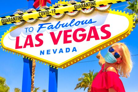 Woman with a surgical mask during Covid-19 pointing Welcome to Fabulous Las Vegas Nevada Sign. Nevada, Unites States during SARS-CoV-2 pandemic epidermis. Coronavirus holidays travel destination.