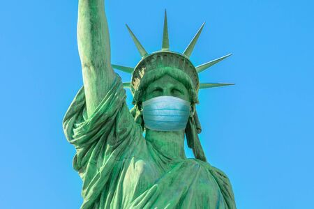 Close up of Statue of Liberty with surgical mask, symbol of New York City at time of Covid-19 isolated. Unites States and SARS-CoV-2 pandemic. USA Coronavirus Quarantine.