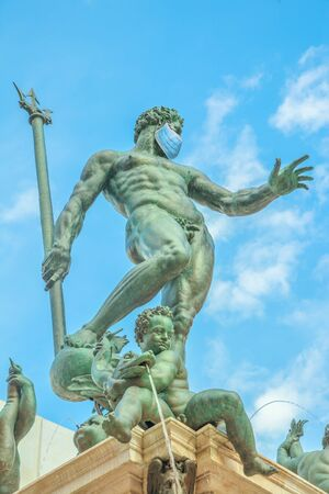 Close up of Statue of Neptune with surgical mask, symbol of Bologna city during Covid-19 time. Italy and SARS-CoV-2 pandemic. Italian Coronavirus Quarantine.