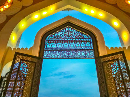 Decorated entrance gate of Grand Mosque in West Bay area, Doha in Qatar. Qatar State Mosque in arab style, Middle East, Arabian Peninsula. Evening sky. Editorial