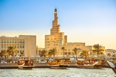 Traditional wooden dhow anchored at Dhow Harbor in Doha Bay with spiral mosque and minaret in the background at sunset. View from Corniche promenade. Qatar, Middle East, Arabian Gulf. Standard-Bild