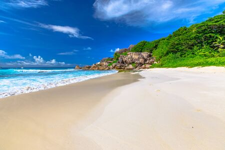 Peaceful perfect postcard of Seychelles beach in La Digue. The white sandy beach and turquoise sea of Grand Anse can be reached by a road in the forest and beside Petite Anse beach. Stock Photo