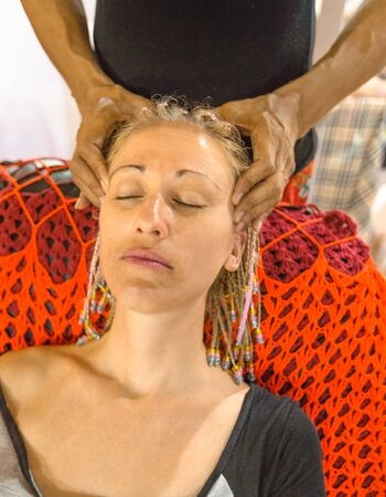 Professional head and facial massage to a young woman in dreadlocks on an armchair in relaxing. Shiatsu massage salon for headache.