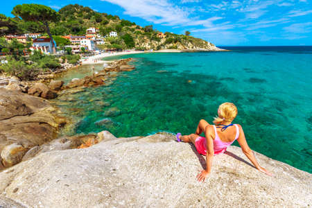 Woman in pink swim suit resting and sunbathing over the stone along Sant Andrea beach, Elba island. Blonde tourist girl on holiday in Italy. Saint Andrew beach popular seaside resort in summer travel