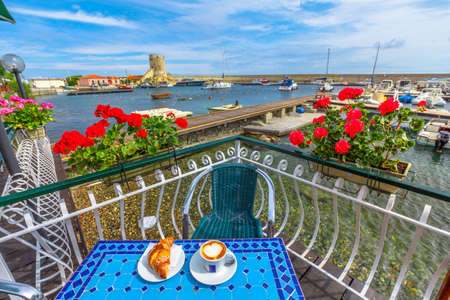 Scenic landscape of red geraniums flowering and breakfast with croissant and cappuccino in Italian cafe. Popular seaside resort Marciana Marina in Elba Island with Torre degli Appiani on background.