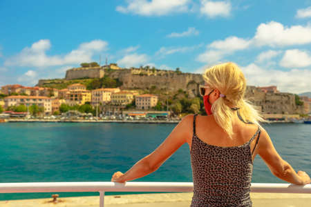 Caucasian blonde woman with a surgical mask during Covid-19 on ferry boat to Elba Island looking Portoferraio city. Italian tourist woman travels on Elba. Coronavirus holiday travel in Europe.
