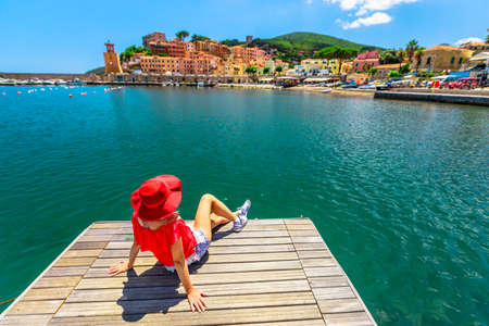 Caucasian woman resting and sunbathing over jetty in Rio Marina harbor of Elba island in red suit. Lifestyle tourist girl on holiday travel in Italy, Europe. Rio Marina skyline cityscape on background Stockfoto