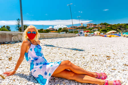 Lifestyle woman sitting on the stone beach with red surgical mask at Le Ghiaie Beach during Covid-19. Tourist in holidays on Elba island. Travel in Italy destination with pandemic from Coronavirus.