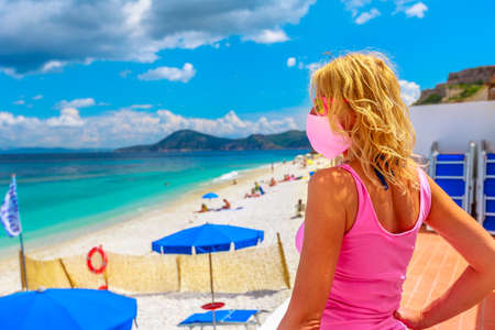 Woman in pink dress and surgical mask on roof top at Le Ghiaie Beach during Covid-19. Tourist during Covid holidays on Elba island. Travel in Italy, Europe destination with pandemic from Coronavirus. Stockfoto