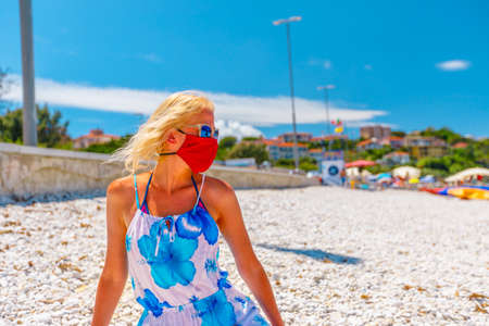 Lifestyle woman with red surgical mask resting at Le Ghiaie Beach during Covid-19. Tourist in holidays on Elba island. Travel in Italy, Europe destination with pandemic from Coronavirus.