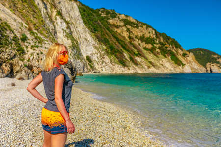 Lifestyle woman with orange surgical mask on Sansone beach during Covid-19 looking the cliffs and turquoise sea. Tourist in Elba island holidays, Tuscany, Italy. Travel with Coronavirus.
