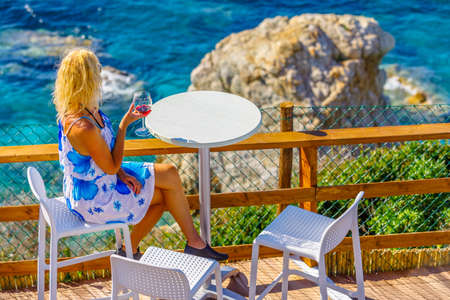 Lifestyle tourist at aperitif drinking a red wine glass and looking large limestone of famous Sansone Beach from panoramic terrace in Elba Island. Blonde woman summer holiday in Tuscany, Italy. Stockfoto