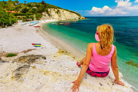 Blonde woman with pink surgical mask sitting on the promontory above Padulella beach near Portoferraio during Covid-19. Tourist in holidays on Elba island, Tuscany. Travel in Italy with Coronavirus. Stockfoto