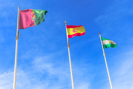 Flags of Andalusia, Granada and Spain, waving in a cloudy sky. Free sky background for copy space and sun shining.