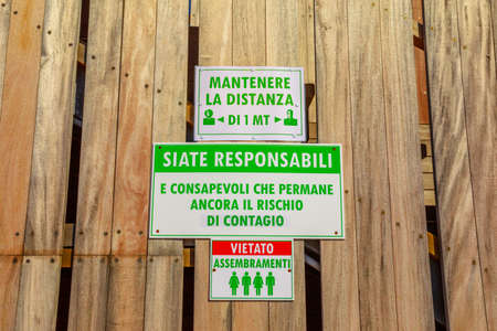 Sansone Beach, Elba island, Italy - June 17, 2020: alert security sign with social distancing rules in a pub of Sansone Beach in Elba Island. summer holiday in Tuscany in Coronavirus COVID-19 epidemic