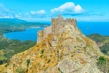 Iconic view of Volterraio Castle on rock at 394 m. Fortress of Volterraio, symbol of Elba Island, dominates Portoferraio Gulf. Panoramic landscape with view from top of Elba mountain. Tuscany, Italy. Banco de Imagens