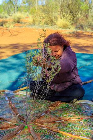 Kings Creek Station, Northern Territory, Australia - Aug 21, 2019: Australian Aboriginal woman making a ritual on a bush painting. Karrke Aboriginal Cultural Experience tour in Australian outback. Redakční
