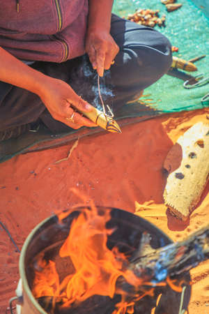 Kings Creek Station, Northern Territory, Australia - Aug 21, 2019: Australian Aboriginal woman shows the traditional hand made local crafts decorated with fire burns. Karrke Aboriginal Cultural tour.