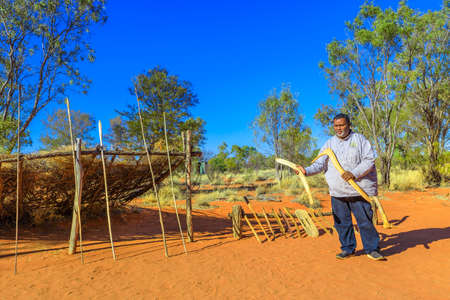 Kings Creek Station, Northern Territory, Australia - Aug 21, 2019: aboriginal Australian man shows a wooden boomerang and typical hunting weapons used by Luritja and Pertame people in Central Australia Redakční