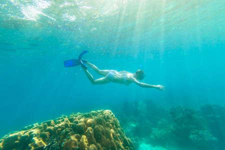Snorkeler female in Ko Surin Marine National Park, underwater scene with sunrays. Woman snorkeling freediving in white bikini in reef of Surin Islands, Andaman Sea, North of Phuket, Phang Nga in Thailand.