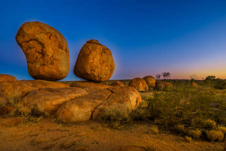 Iconic Devils Marbles: Eggs of mythical Rainbow Serpent on evening twilight sky. Karlu Karlu is one of Australia's most famous natural wonders in Northern Territory, Outback Red Centre.