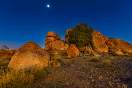 Nocturnal australian outback landscape of Devils Marbles granite boulders by night. Karlu Karlu - Devils Marbles Conservation Reserve in Northern Territory, Australia. Moon in the sky.
