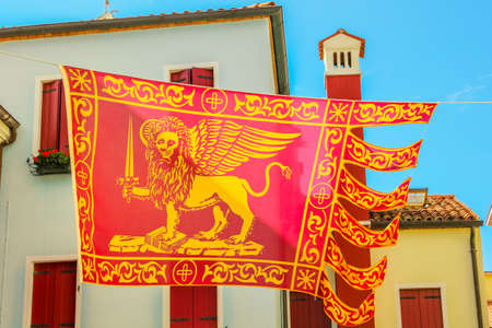 Close-up of San Marco flag, saint Marco, in Italy waving on urban background with Italian style architecture. Red flag of Venice city and Veneto region, with a golden-winged lion.