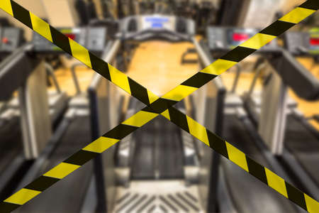 Concept of gyms closure for Coronavirus pandemic. Covid-19 quarantine lockdown of sports activities indoor. A row of treadmills in modern gym blurred background.