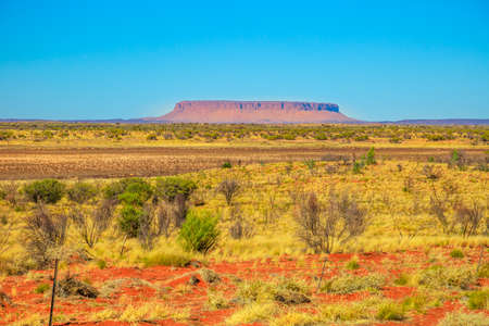 Iconic table mountain or Mount Conner often mistaken for Uluru. It is located near Kings Canyon Watarrka National Park. Red desert landscape in Australia Outback Red Center, Northern Territory.