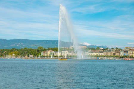 View of Jet deau fountain or water jet fountain, harbor and Geneva Lake. The most famous attraction and symbol of Geneva. Swiss Alps and skyline cityscape, on background. French Swiss Switzerland