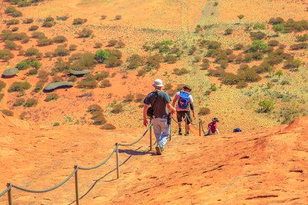 Uluru, Northern Territory, Australia - Aug 23, 2019: Climbers descend Uluru into Kata Tjuta National Park against the wishes of the aboriginal people Anangu land owners.