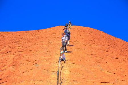 Uluru, Northern Territory, Australia - Aug 23, 2019: Climbers ascend Uluru in Kata Tjuta National Park against the wishes of the aboriginal people Anangu land owners. Editorial