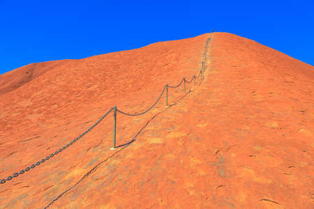 Uluru, Northern Territory, Australia - Aug 23, 2019: safety chain, 138 steel posts, painted guidelines along Ayers Rock in Uluru-Kata Tjuta National Park. The October, 26, 2019 the climb will be closed