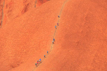 Uluru, Northern Territory, Australia - Aug 26, 2019: people climb on Ayers Rock. Climbing Uluru is sacred to Anangu people, the traditional owners of Uluru-Kata Tjuta and very dangerous.