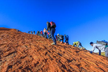 Uluru, Northern Territory, Australia - Aug 23, 2019: crowd of people climbing on Ayers Rock in Uluru - Kata Tjuta National Park before 26 October 2019 when the climb will be closed permanently.