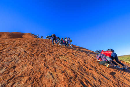 Uluru, Northern Territory, Australia - Aug 23, 2019: many people climb on Ayers Rock. Climbing Uluru is sacred to Anangu people, the traditional owners of Uluru-Kata Tjuta and very dangerous.
