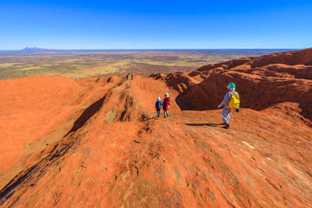 Uluru, Northern Territory, Australia - Aug 23, 2019: people descend along the painted guidelines over top of Ayers Rock in Uluru-Kata Tjuta National Park. Mount Olga rock formation on background. Editorial