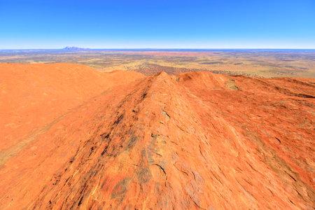 Uluru, Northern Territory, Australia - Aug 23, 2019: view from the top of Uluru-Kata Tjuta National Park. Climbing to Uluru summit. In the background Mount Olga or Kata Tjuta domed formation.