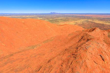 Uluru, Northern Territory, Australia - Aug 23, 2019: panoramic view from the top of Uluru-Kata Tjuta National Park. Climbing to Uluru summit. In the distance Mount Olga or Kata Tjuta domed formation