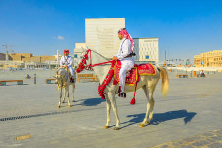 Doha, Qatar - February 20, 2019: two heritage Police Officers in traditional Qatari uniform riding white Arabian Horses at square of Souq Waqif. Popular tourist attraction in Doha city center. Editorial